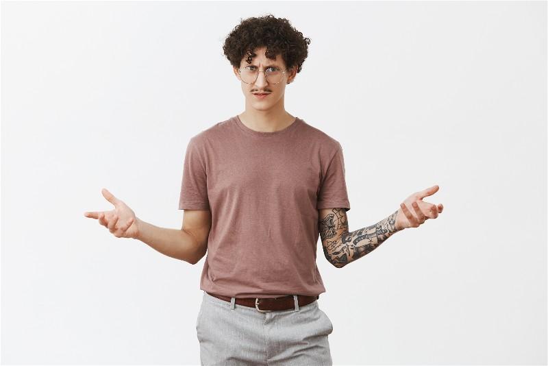 Homem parado com os braços abertos com uma expressão de dúvida