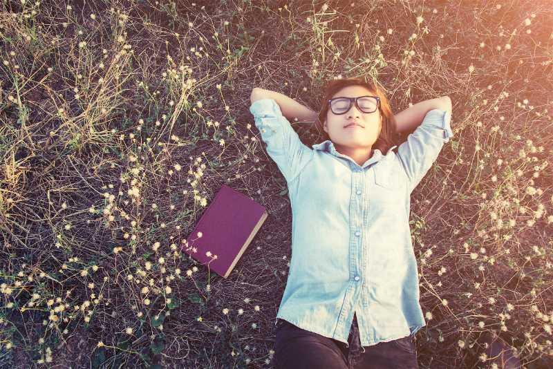 Mulher deitada em gramado ao lado de livro
