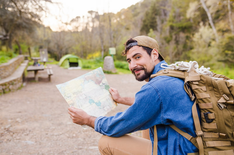 Homem agachado com mochila nas costas e segurando um mapa