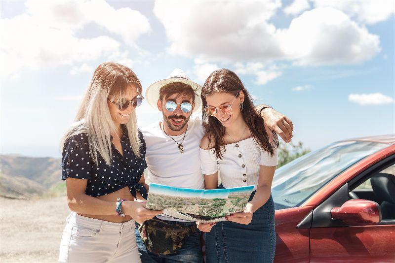 Três amigos juntos, sorridentes e olhando em mapa